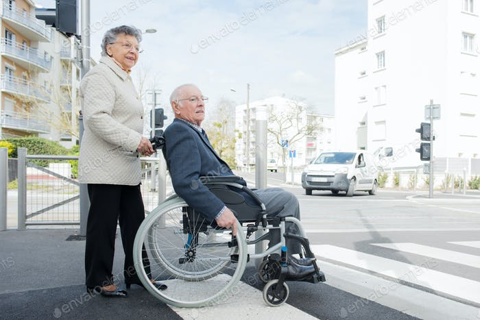 Elderly lady pushing husband in wheelchair across road