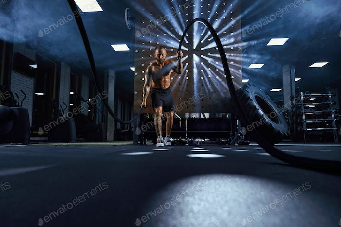 Muscular shirtless sportsman training with ropes