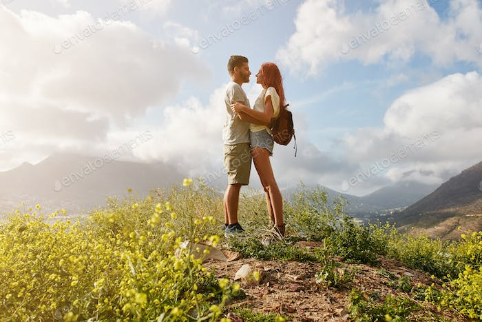Amorous couple in embrace standing on a hill top