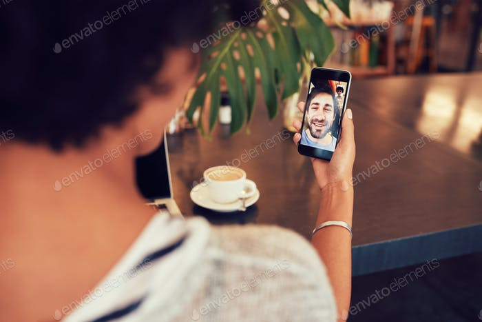 Woman having a videochat with friend on mobile phone.