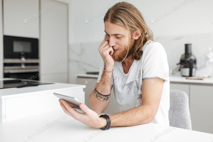 Young man sitting with digital tablet in hand in kitchen at home