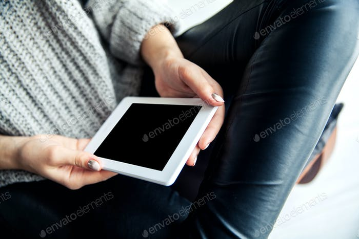 A girl holding a tablet in hands, reader with a nice manicure. Leather trousers, ugg boots. Fashion