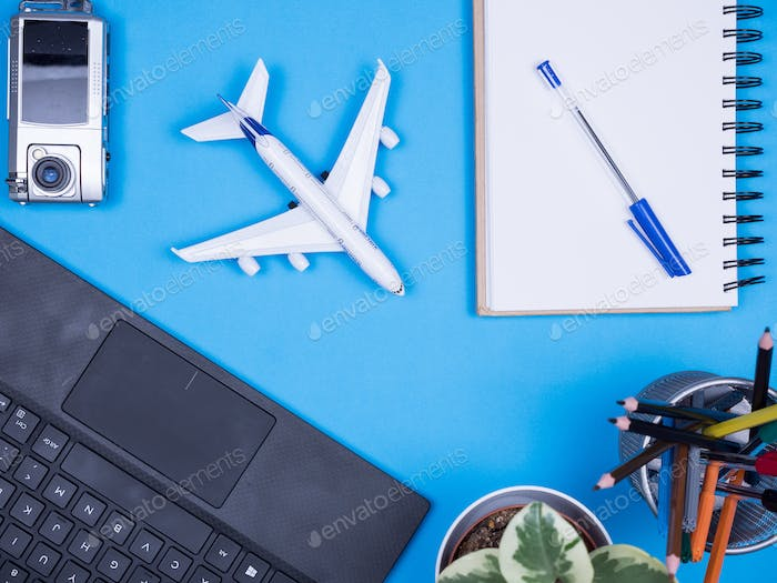 Flat lay top view of modern traveler over blue background