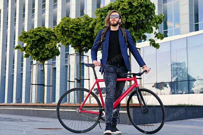 A man with backpack sits on the red fixed bicycle.