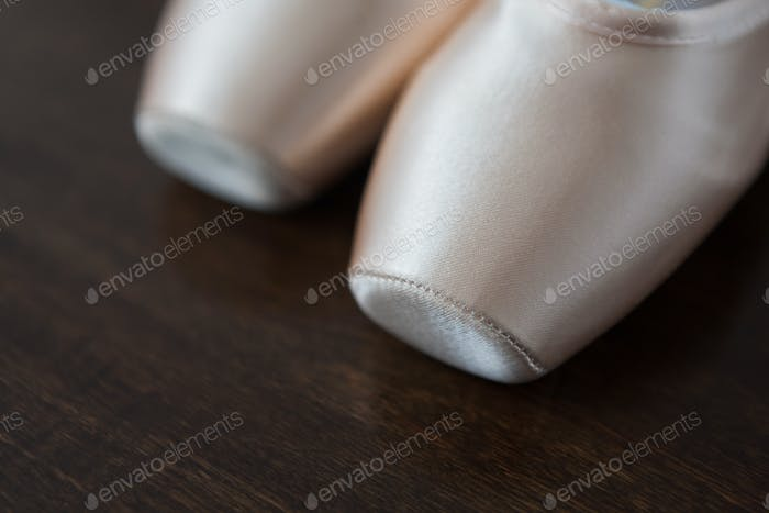 Pink ballet pointe shoes closeup on dark wood background