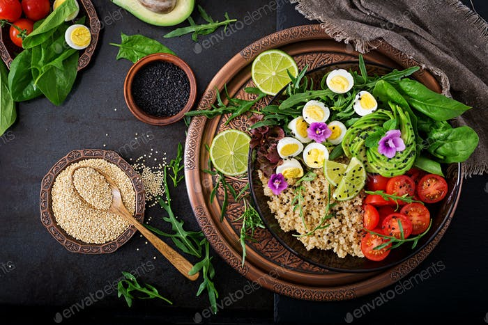Healthy salad of fresh vegetables - tomatoes, avocado, arugula, egg, spinach and quinoa on bowl
