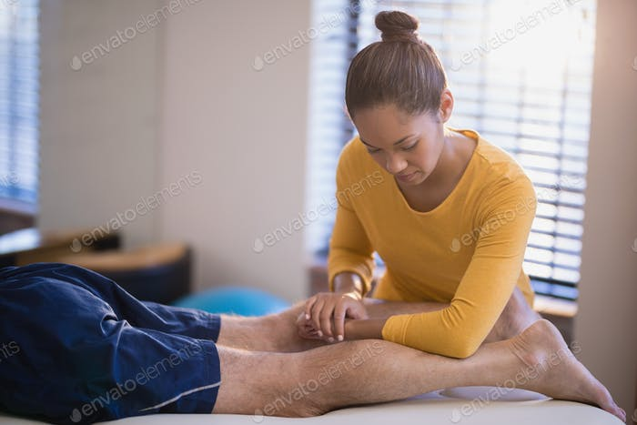 Young female therapist massaging calf of senior male patient