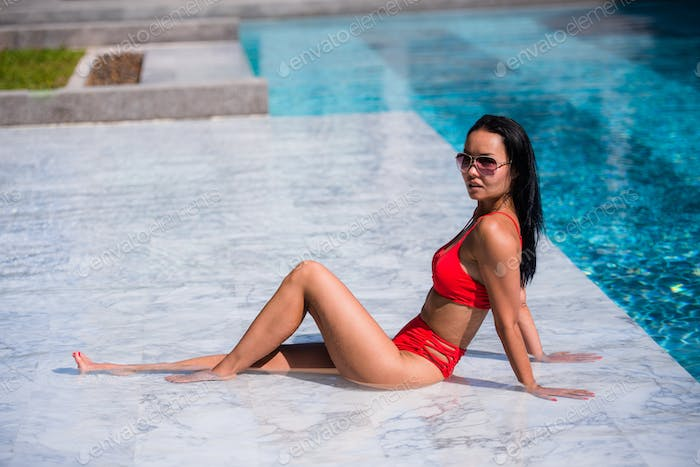 Elegant sexy woman in the red bikini on the sun-tanned slim and shapely body is posing near the