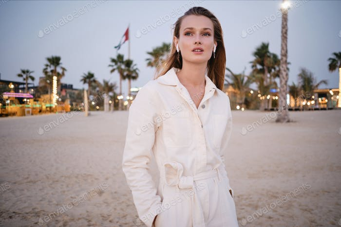 Gorgeous model in wireless earphones thoughtfully looking aside on beautiful beach