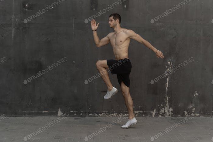 Junger Sportler, nackter Torso, läuft gegen eine graue Wand
