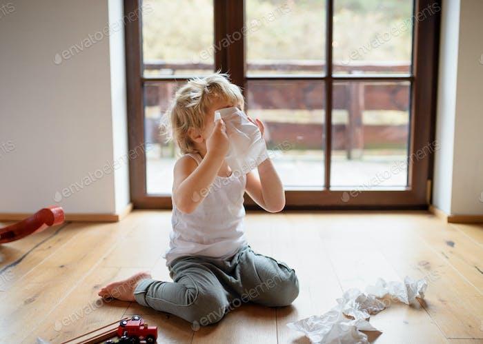 Маленький больной мальчик с холодом дома сидит на земле, чихает