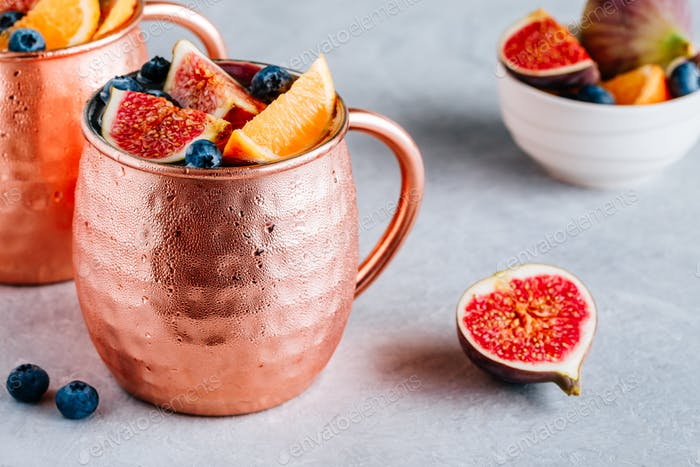 Fig moscow mule ice cold cocktail in copper cup with blueberries and orange