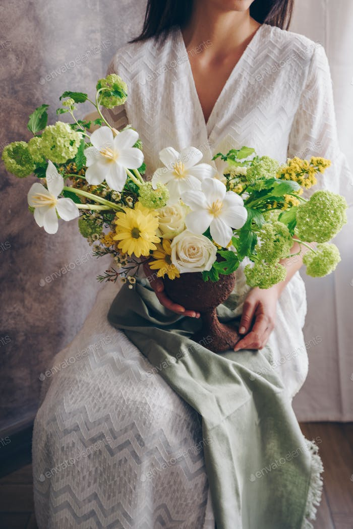 Young woman in a white dress holding vase with flowers. Vintage,