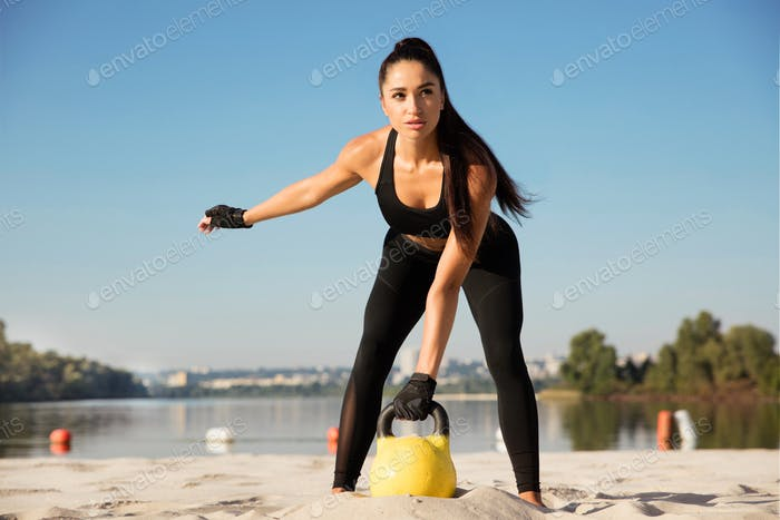 Young healthy female athlete doing workout at the beach