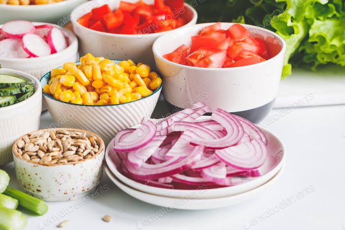 Assortment ingredients for healthy vegetarian salad in different portion bowls on a table