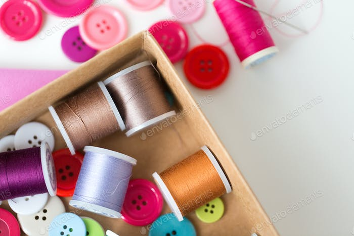 box with thread spools and sewing buttons on table