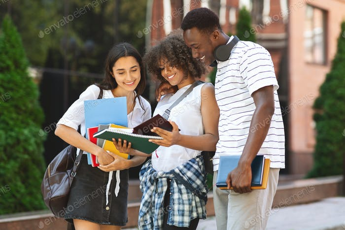 Smiling multiethnic students standing outdoors, checking college curriculum together