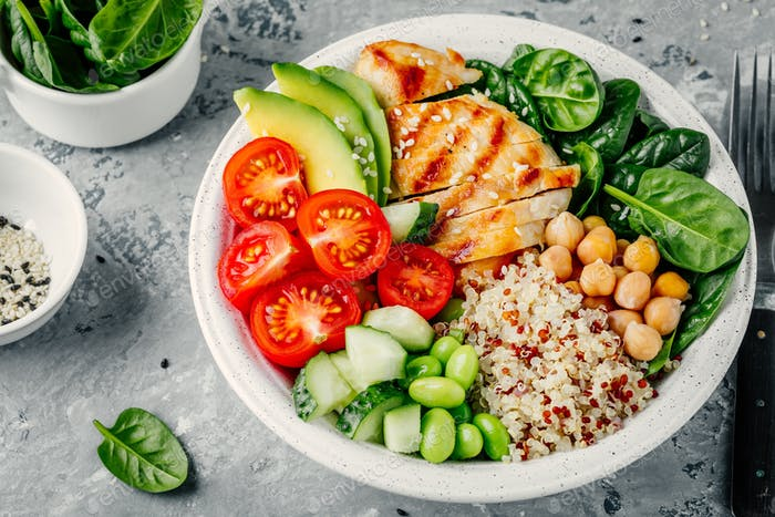 Buddha bowl with spinach salad, quinoa, chickpeas, grilled chicken, avocado, tomatoes, cucumbers
