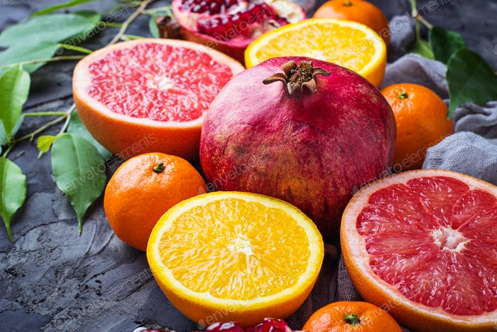 Dissected fresh fruits. Pomegranate, orange, grapefruit and tangerines