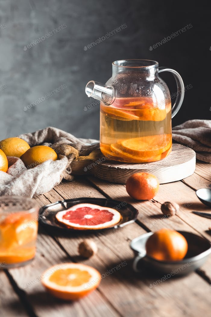 Zitrustee in einer transparenten Teekanne auf einem Tisch mit Grapefruit und auf einem Holztisch. Gesundes Getränk