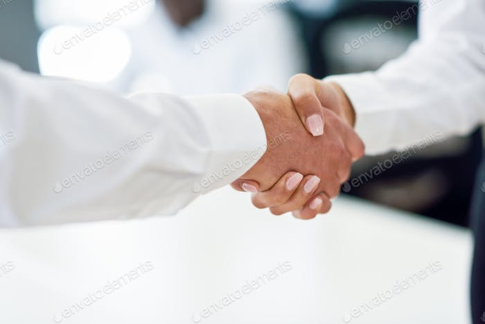 Caucasian businessman shaking hands with businesswoman in an off