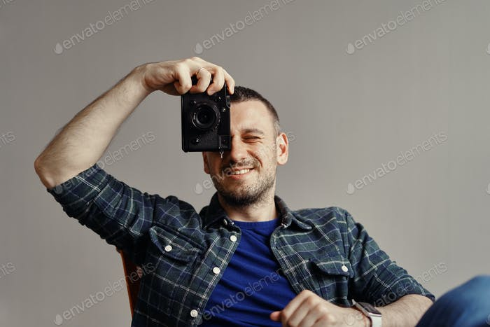 Photographer taking picture while looking to camera
