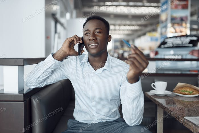 Schwarzer Geschäftsmann telefonisch, Auto-Showroom