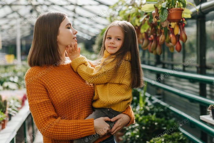 Pretty child touching mother's face. Stylish woman posing with kid in orangery