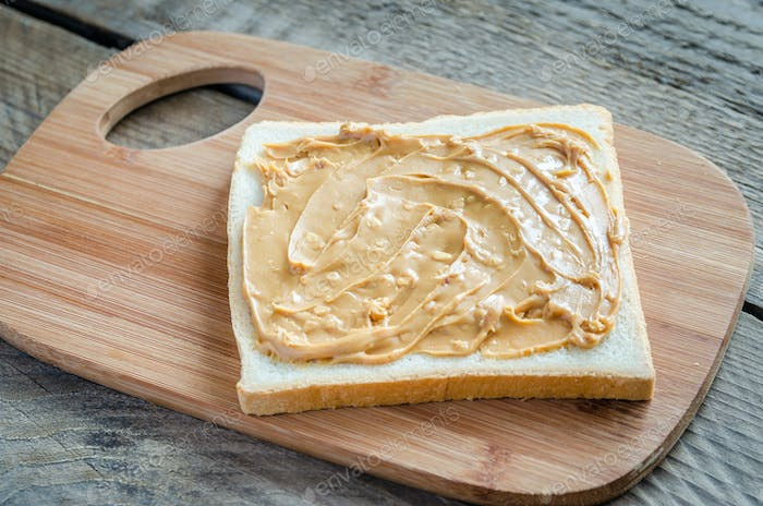 Sandwich with peanut butter on the wooden board