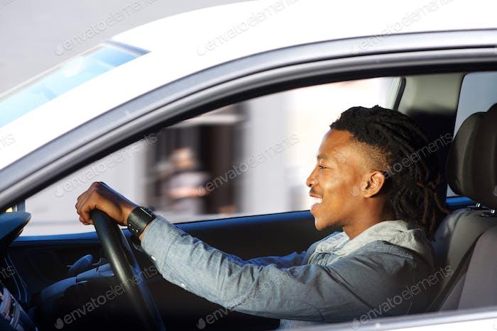 happy young black man driving car