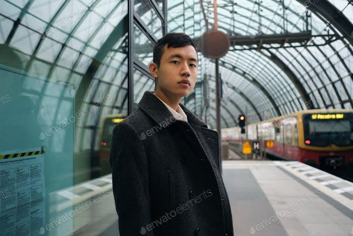 Young serious Asian businessman in coat waiting train at city subway station