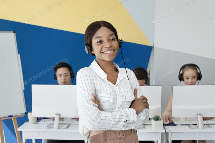 African American female tech support operator looking at camera and smiling at call centre