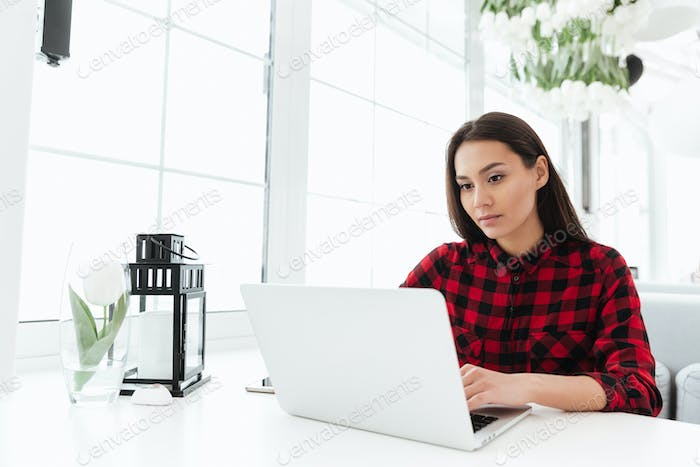 Young woman sitting in light cafe and using laptop