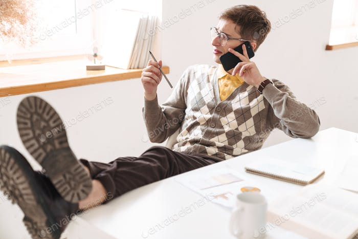 Confused young guy student talking by mobile phone