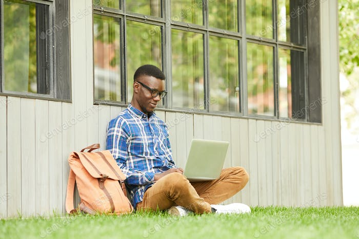 African Student Using Laptop Outdoors