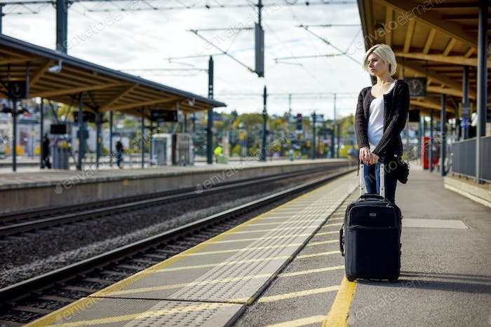 Woman With Luggage Waiting On Platform Of Railroad Station
