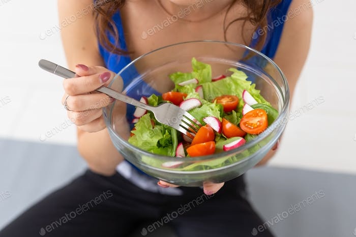 Healthy lifestyle, food concept - close up of a plate of salad in woman's hands
