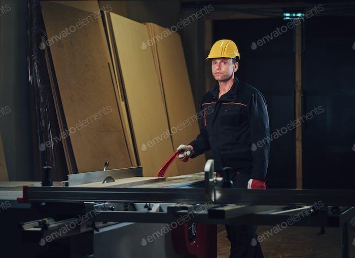 Zimmermann lehnt sich an den Holztisch.
