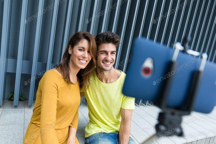Junges kaukasisches Paar verwenden Selfie-Stick für das Fotografieren