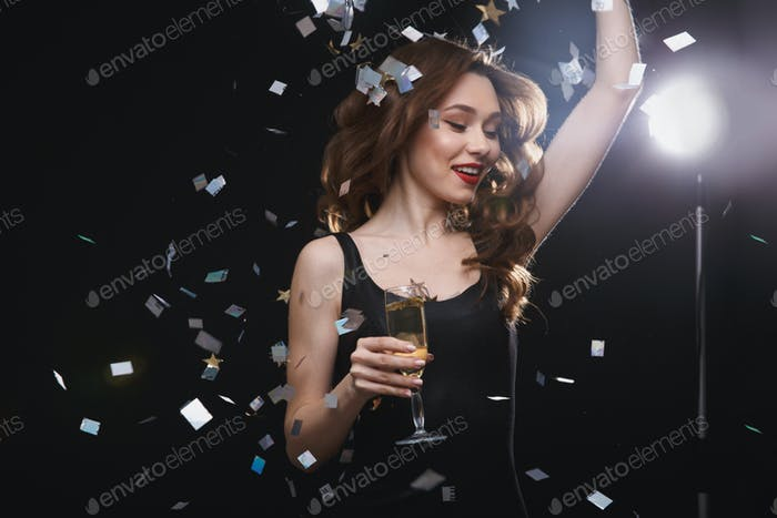 Happy woman with glass of champagne dancing and having fun