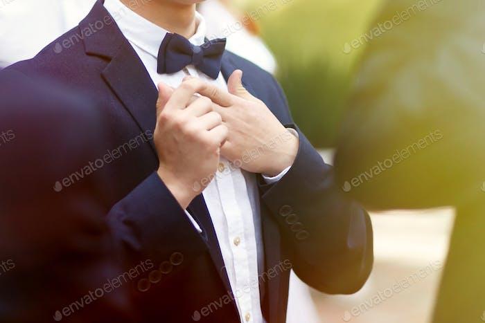 стильный уверенный мужчина в костюме и боути, прием на роскошной свадьбе