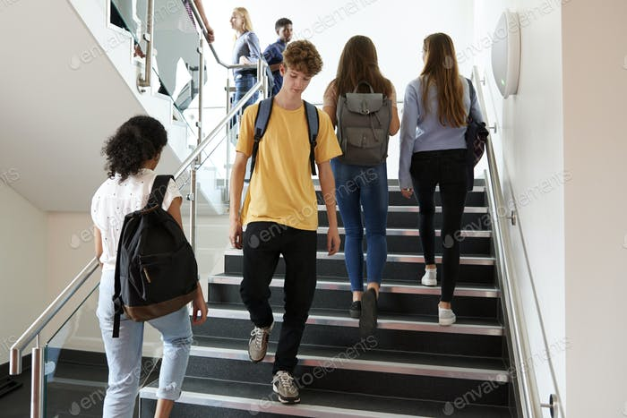 High School Students Walking On Stairs Between Lessons In Busy College Building