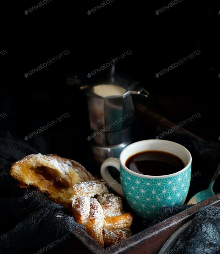 Cup of coffee with croissant on a dark background close up