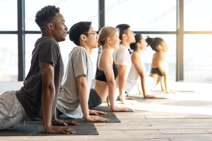Side View Of Sporty Multiethnic People Practicing Yoga In Cobra Pose