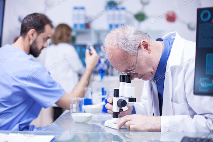 Senior scientist wearing a white coat doing advanced analysis under microscope
