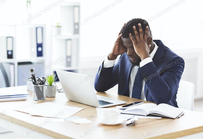 Stressed african businessman sitting in office with hand on forehead