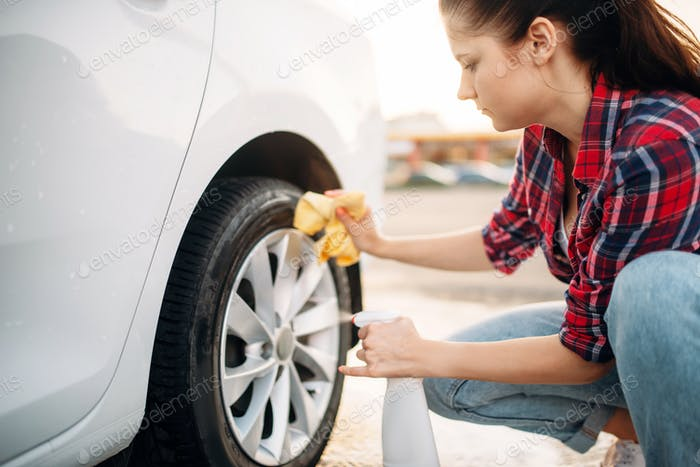 Woman cleans wheel disk of the car with spray