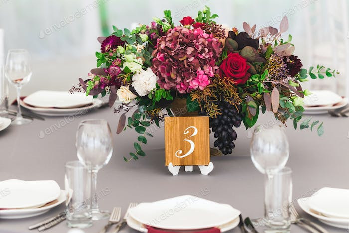 Beautiful red bouquet with hydrangea on wedding table with wooden plate with number of table