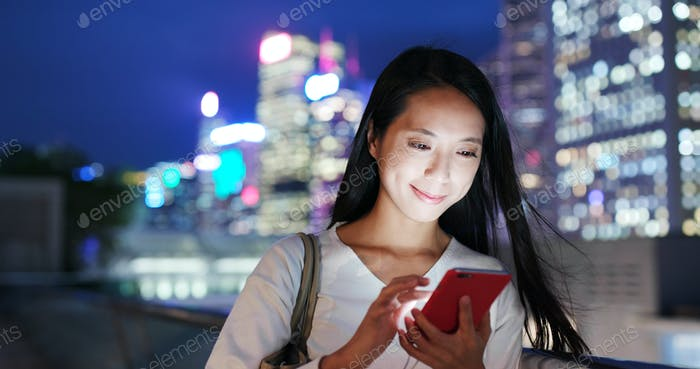 Woman use cellphone online at night