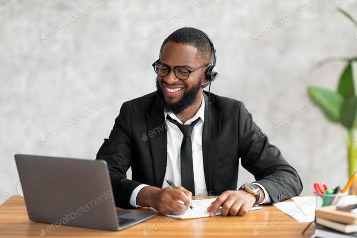 African American man using laptop writing in notebook